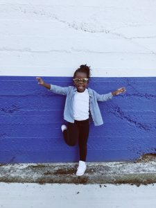 Little girl smiling while standing against a wall, peace