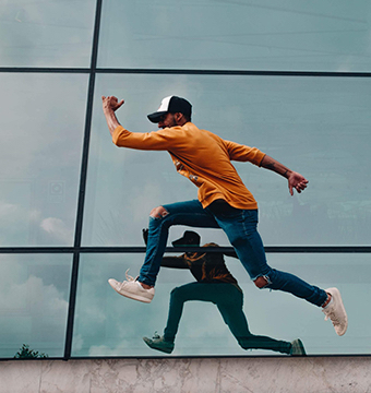 Happy Man Jumping in Front of Building